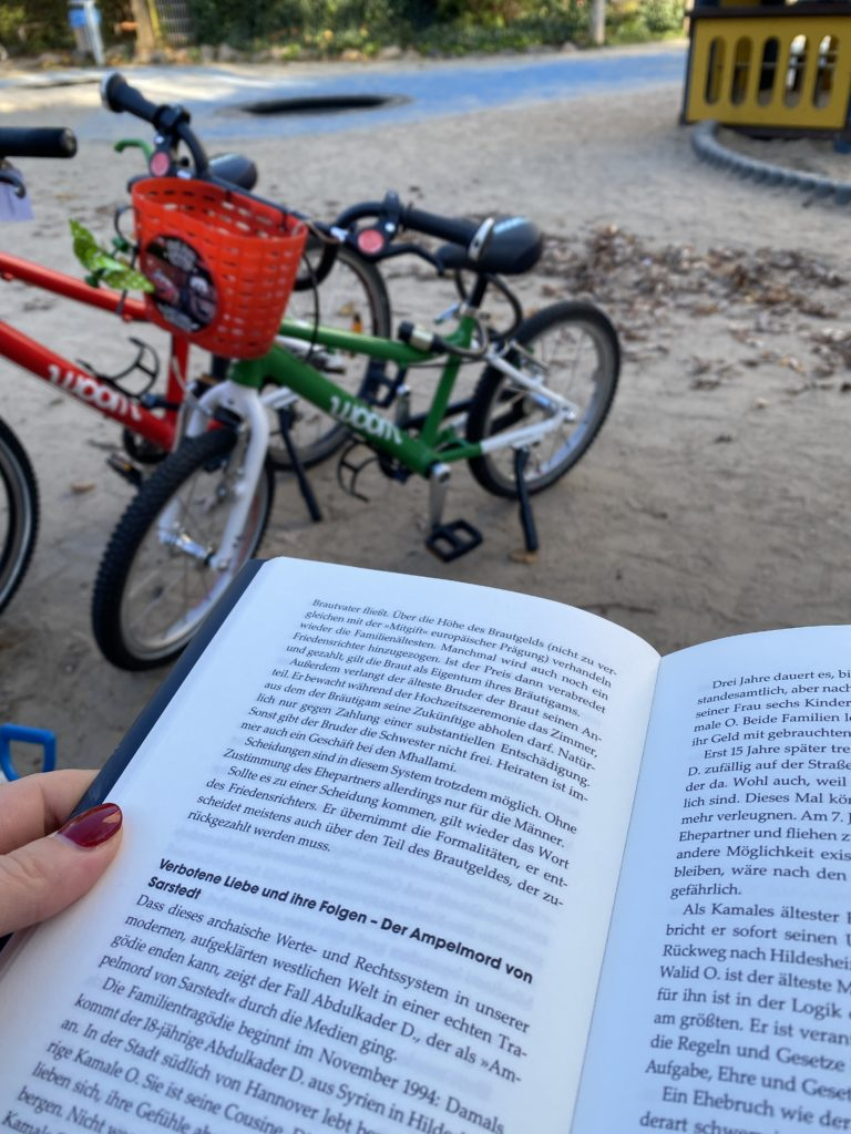 Auf dem Spielplatz ein Buch lesen und den Kindern beim Spielen zuschauen