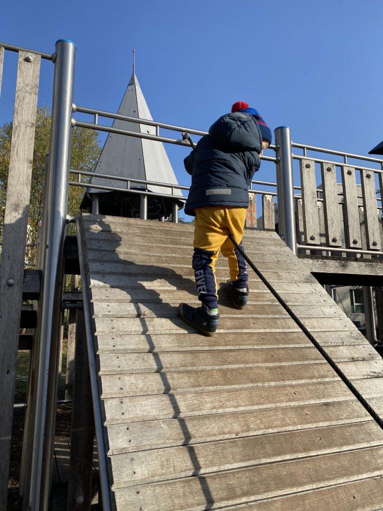 Junge klettert eine Kletterwand hoch